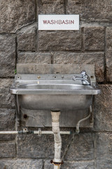 Steel sink hang on stone wall on street in city center. The empty public bathroom in Hong Kong.