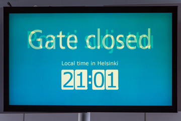 The multilingual inscription changes on the screen. The monitor at gate at the airport Helsinki, Finland. Closed gate at the terminal.