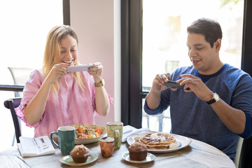 Couple photographing breakfast in restaurant