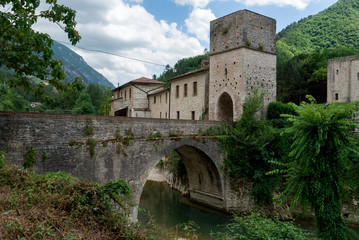 Medieval village with stone bridge over a river. Genga, Italy