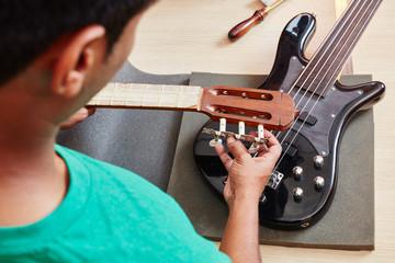 Mann bei der Reparatur einer E-Gitarre