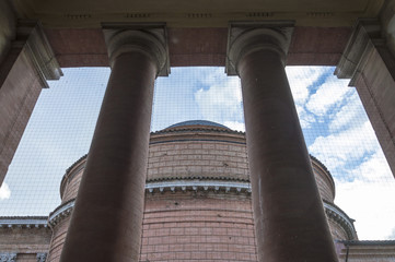 Architectural detail of columns of stone material. Background with a big dome.
