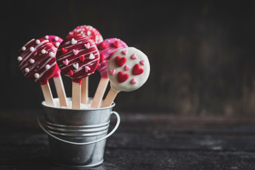 Love cake pops in basket on the wooden background with blank space,valentines day concept and selrctive focus