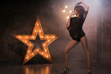 red-haired sexy young woman dancing against a background of glowing stars and lamps