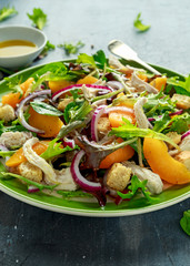 Fresh salad with chicken breast, peach, red onion, croutons and vegetables in a green plate. healthy food