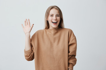 Friendly positive blonde female smiling broadly and happily camera, dressed in loose sweater, greeting her friends, pleased to meet them. Positive emotions, feelings and face expression. Wall mural
