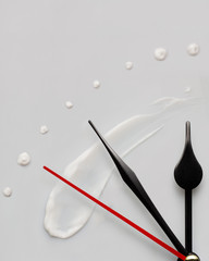 Beauty time / Creative concept photo of clock hands and cream on gray background.