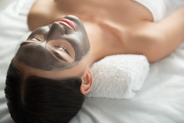 Serene young woman is lying at spa with relaxation. Focus on her face with mask