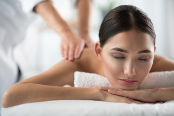 Portrait of serene young woman enjoying massage at wellness center. Her eyes are closed with satisfaction. Peace and comfort concept