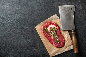 Raw rib eye steak and butcher knife on blackboard