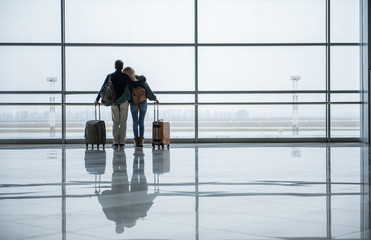 Wall Mural - Two young people embracing while looking at the beautiful view from the airport window. Copy space in right side
