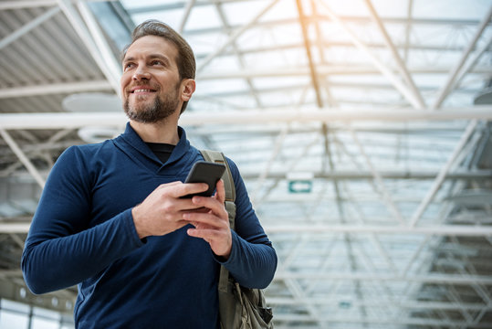 Low angle of cheerful man holding smartphone in hands. He is looking aside and smiling. Copy space in right side