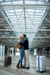 Joyful man and woman meeting at the airport. They are embracing each other. Baggage is aside
