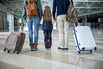 Low angle of adults standing at the airport after disembarkation. They are keeping few suitcases and their kid close to themselves. Focus on their back
