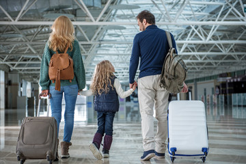 Wall Mural - Glad parents and child passing terminal after plane landing. They are holding hands. Focus on their back