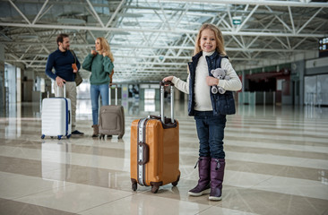 Full length portrait of laughing girl standing with baggage ahead of parents. Focus on child