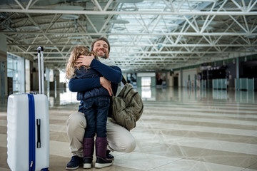 Wall Mural - Daddy is embracing girl in the airport hall with happiness. Copy space in right side