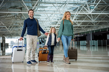 Wall Mural - Full length of happy family walking through airport. Everyone carrying own suitcase