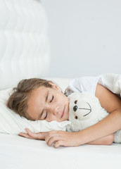 Sleeping girl hugging a toy bear. Space for text
