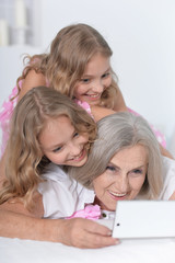 granny with granddaughters using smartphone