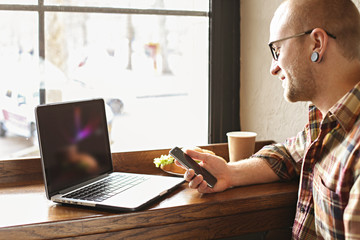 Smiling bearded businessman wearing casual hipster clothing using laptop and cell smartphone in coffe house.
