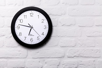 Wall clock on white brick wall