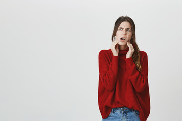 Portrait of fashionable young female wearing red winter sweater having toothache over white background. Dental and health care concept. Model feels pain and thinks about visiting dentist