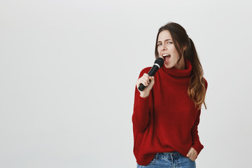 Portrait of stylish beautiful girl singing in karaoke, holding microphone, wearing cute red winter sweater over white background. Young female performing in front of audience