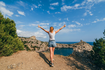 happy traveler girl with raised hands standing on top of a mountain above the sea in the summer holiday