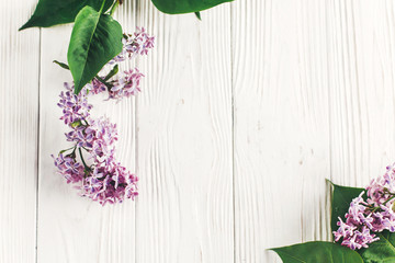 hello spring flat lay image. beautiful lilac flowers on rustic white wooden background top view. space for text. greeting card. earth day. happy mothers woman day. eco