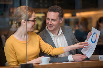 Outgoing male and cheerful girl discussing information of document. Job concept