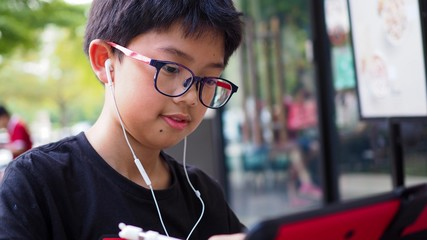 Asian boy drawing on digital tablet with head phone.
