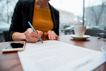 Close up girl hand putting signature on document. She situating at desk. Business concept. Low angle