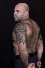 Big bald hairy powerlifter with polinesian tatoo on the shoulders