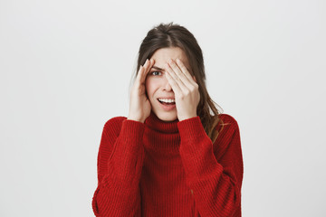 Portrait of young attractive woman with brown hair peeking while covering one eye with hand, isolated over white background. Girl feels embarrassed though she is interested so she keeps staring.