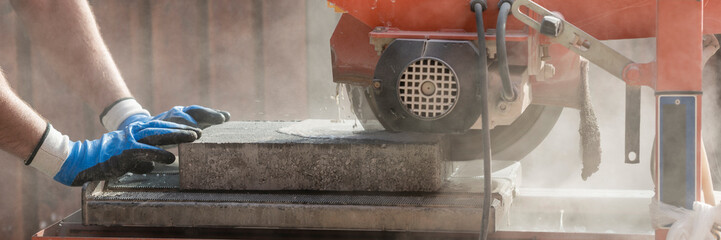 Wide panorama view of a building contractor using an angle grinder outdoors