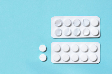 Full and used white blister pills on a blue background. Medications
