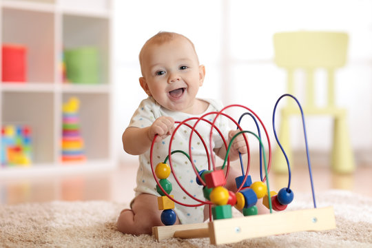 Adorable baby playing in nursery. Happy healthy child having fun with colorful toy at home.