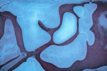 Natural background. Frozen water. Abstract pattern formed on a frozen puddle.