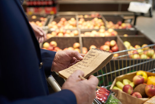 Close up of senior man holding shopping list while grocery shopping in supermarket, fruits and vegetables in background, copy space