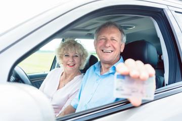 Senior Mann zeigt seinen Führerschein im Auto