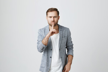 Angry serious bearded male model dressed in fashionable clothes, keeps index finger on lips, demands complete silence, isolated against gray background. Man demonstrates hush sign indoors