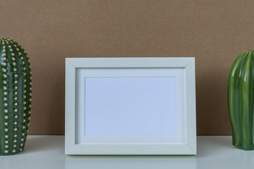 A white desk with two green cactus and a white frame with space for text on the background of a brown empty wall