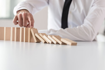 Businessman in white shirt stopping domino effect