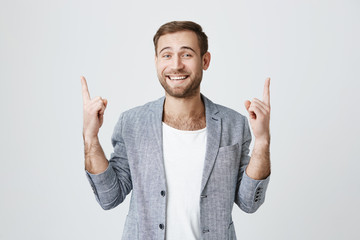Advertising concept. Excited cheerful european bearded man wearing stylish clothes and smiling broadly, pointing index fingers upwards, motivating and attracting customers.