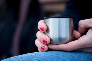 Junge Frau mit roten Fingernägeln hält Kafee (Thermobecher) in der Hand