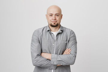 Bald handsome man with beard and crossed hands standing over white background. Person in casual clothes waiting in queue to order cup of coffee and brighten up his morning.
