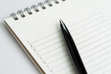 Personal to do lists or new year's resolution concept by closed up of list of numbers on white clean notepad with pen on it