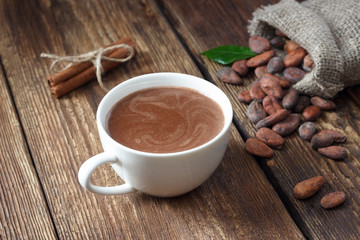 Cocoa drink in white mug and cocoa beans on wooden table.