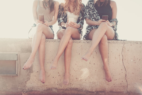 Three young woman legs with no visible faces using mobile phone. modern related internet and social networks image with beautiful people using technology